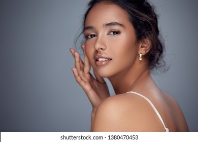 pretty girl with open shoulder touching her cheek