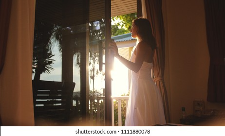 Pretty girl opens the door in the early morning during sunrise with lens flare effects and look out to the shining sun