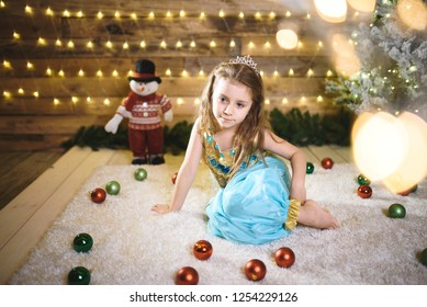 pretty girl in oriental blue suit of princess sitting among christmas balls