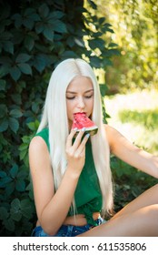 pretty girl outdoors eating fresh watermelon