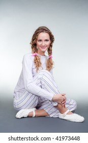 pretty girl in pajamas and slippers sitting on the floor