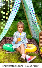 Pretty girl with picnic basket sitting in meadow in a tent