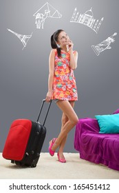Pretty girl planning her travel abroad with chalk images against a gray background