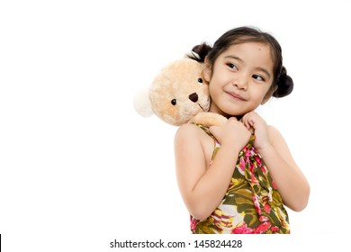 Pretty girl playing with bear doll on white background