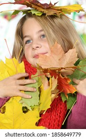 Pretty girl playing with a bunch of multicolored autumn leaves on a white background