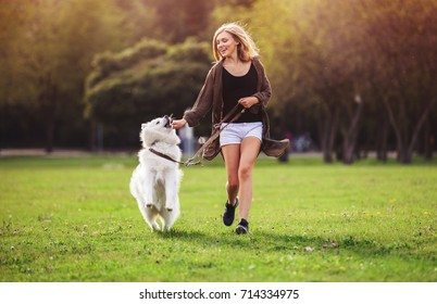 Pretty girl playing and running with samoyed dog at the park outdoor