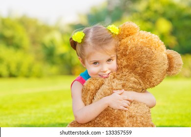 Pretty girl playing with soft toy outdoor, cute infant having fun on backyard in spring time, happy childhood concept