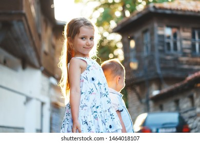 pretty girl posing to camera close to brother