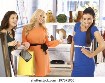 Pretty girl posing in new blue dress at clothes store, friends looking at her happy, all smiling.