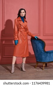 Pretty girl is posing next to a blue armchair on the coral wall background in a studio. She wears a leather orange trench, blue sweater and light blue gloves, brown shoes. Woman looks to the side.