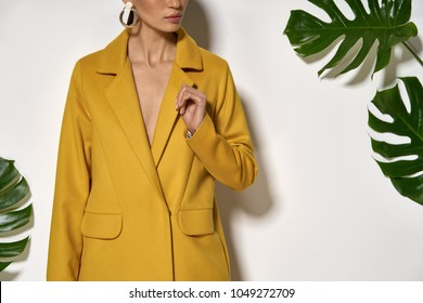 Pretty girl is posing in a studio on a background of a white wall with big green leaves. She wears a mustard coat. Woman holds her left hand next to the chest. Closeup. Horizontal.