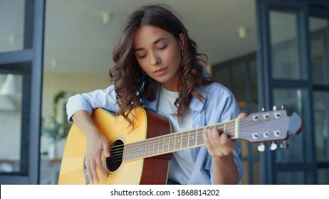 Pretty girl practicing music on guitar. Female guitarist playing chords on acoustic guitar in living room. Happy woman showing yes gesture with hand. Positive lady enjoying success at home