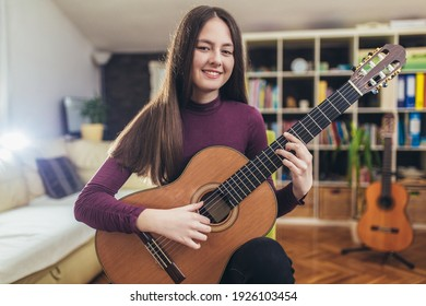 Pretty girl practicing some new sound on a guitar at home