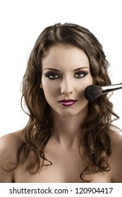 pretty girl with purple make-up and wavy hair and brushes, she looks in to the lens and smiles