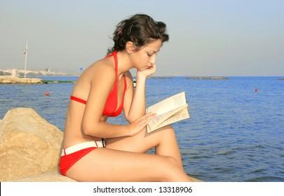 Pretty girl reading book on the beach.