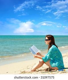 Pretty girl reading novel at beautiful beach