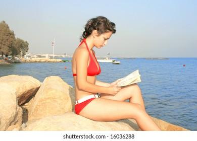 Pretty girl in red bikini with book on the beach.