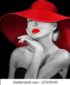 pretty girl in red hat with red lipstick on lips looking at camera