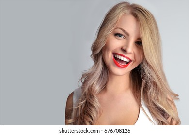 Pretty girl with red lips and professional make up and white teeth smile