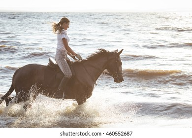 Pretty girl riding horse in river water