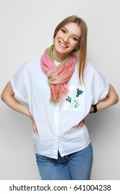 Pretty girl in rolled up jeans, gumshoes and colorful silk scarf posing on white background
