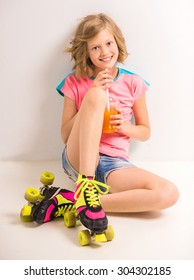 Pretty girl in roller skates drinking juice while sitting on a floor at studio against white background.