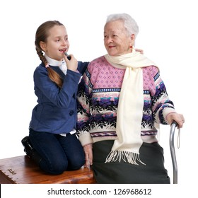 Pretty girl rouging her lips and sitting with her  grandmother on a box