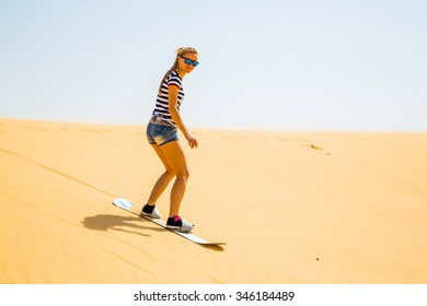 Pretty girl sand boarding down the dunes in a desert near Abu Dhabi