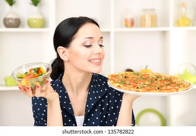 Pretty girl selects pizza or diet on kitchen background