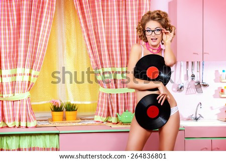 835a6e7c714 Pretty girl in sexy lingerie alluring with vinyl records on her glamorous  pink kitchen. Fashion