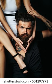 Pretty girl with sexy slim legs sits on shoulder of handsome man hipster graying brunette with long beard and moustache with swallow tattoo