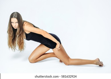Pretty girl or sexy woman with long brunette hair in sexy black dress crawls on knees on floor isolated on white background