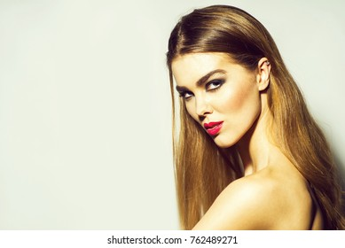 Pretty girl or sexy woman with red lips, stylish makeup, on beautiful face and long hair on grey background, copy space