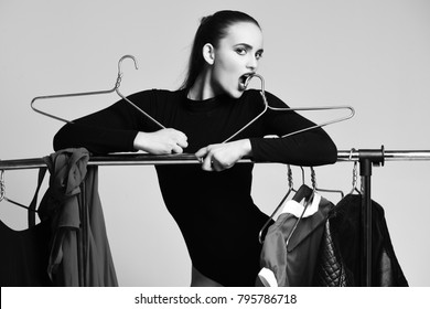 Pretty girl or sexy woman, slim fashion model, with sexi blue lips in black bodysuit posing at clothing rack with colorful clothes, dresses on hangers, wardrobe, on grey background