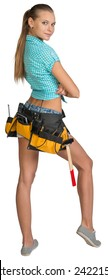 Pretty girl in shorts, shirt and tool belt with tools standing with crossed arms. Full length rear view. Isolated over white background