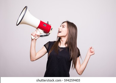 Pretty girl shouting into megaphone on copy space