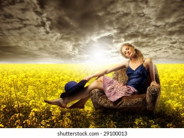 pretty girl sited on armchair in a field of yellow flowers