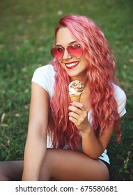 Pretty girl siting in park and holding ice cream