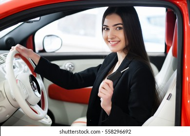 pretty girl sitting in a car and smiling, buying a car, red car, keys in hand