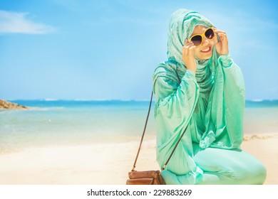 pretty girl sitting on a beach wearing traditional muslim costume