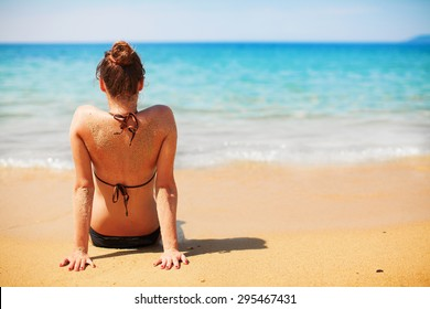 Pretty girl sitting on a beach in a bikini and enjoying in view of the open sea.