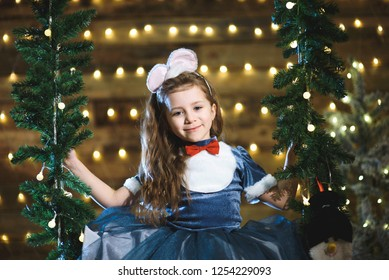 pretty girl sitting on seesaw in christmas lights
