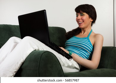 Pretty girl sitting on a sofa and working on her laptop.