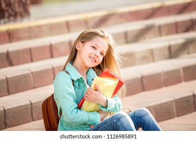 pretty girl sitting on the steps of a school with books and smiling.