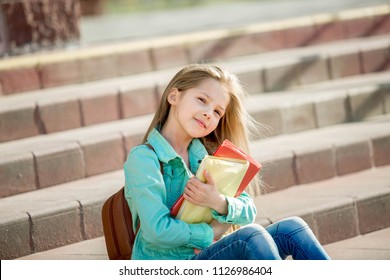 pretty girl sitting on the steps of a school with books