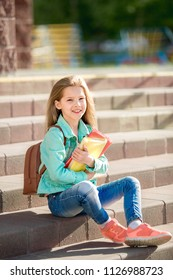 pretty girl sitting on the steps of a school with books and smiling