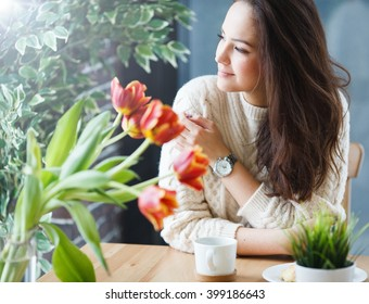 A pretty girl is sitting and waiting for someone. She is drinking some coffe or tea and eating croissants or some bakery cakes.