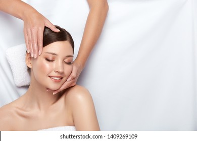 pretty girl with smile lying on the white towel and having facial massage, copy space, spa procedures with happy clients