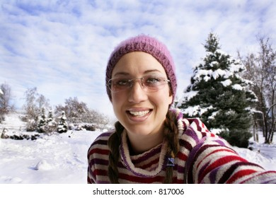 Pretty girl smiles into the camera in the snow.