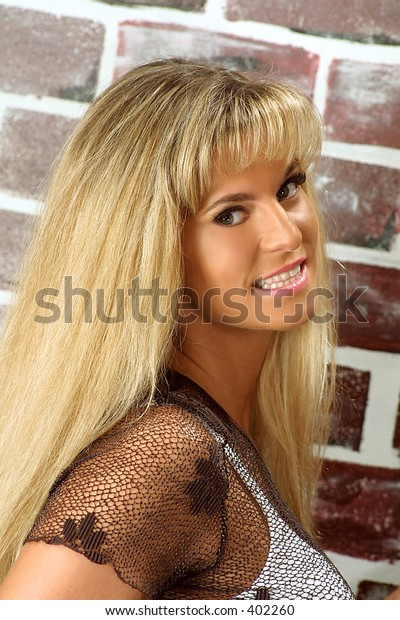 pretty girl smiling in front of a brick wall